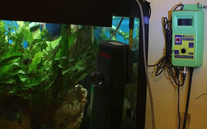 Detalle de la instalación de un peachímetro digital en un acuario.