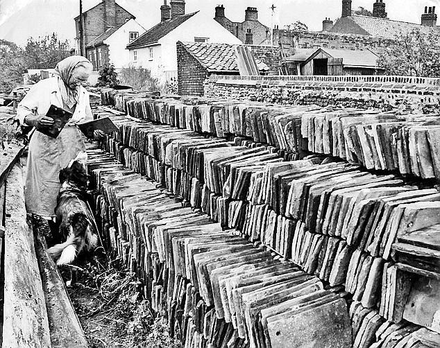 La anciana clasificando las tejas de su casa.